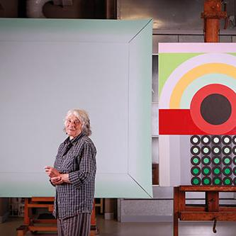 Artist Janet Dawson with two paintings to be displayed at NGV's 'The Field Revisited' exhibition. Photo courtesy of NGV.